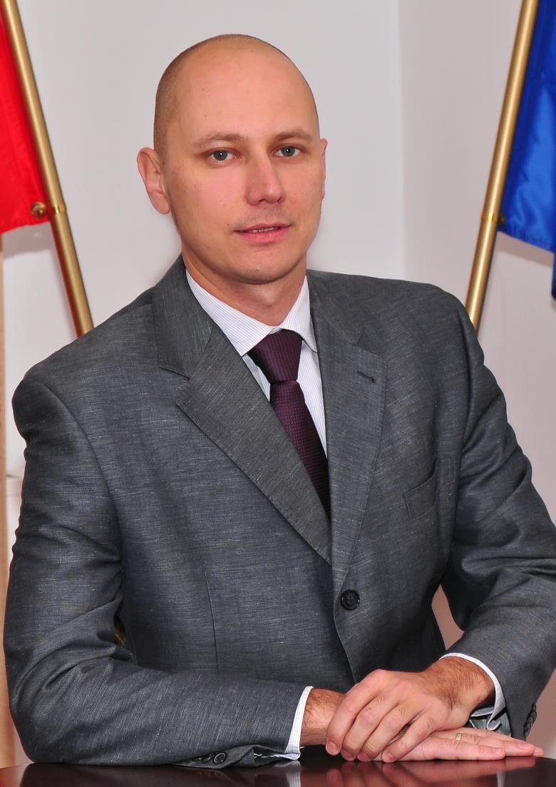 Mężczyzna w garniturze na tle polskiej i unijnej flagi