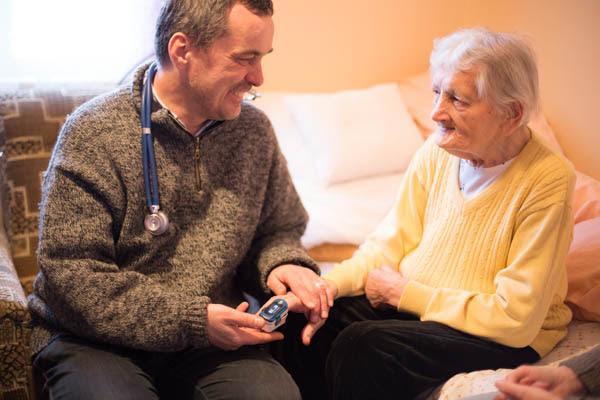mężczyzna ze stetoskopem trzyma za rękę starszą kobietę