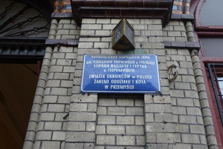 Ściana z niebieską tablicą z napisem po polsku i ukraińsku, że tu się mieści oddział Związku Ukraińców w Polsce