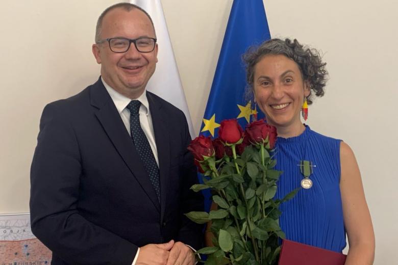 Uśmiechnięty mężczyzna i kobieta z kwiatami, z przypiętym medalem
