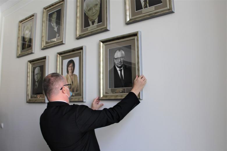osoba zawiesza zdjęcie na ścianie