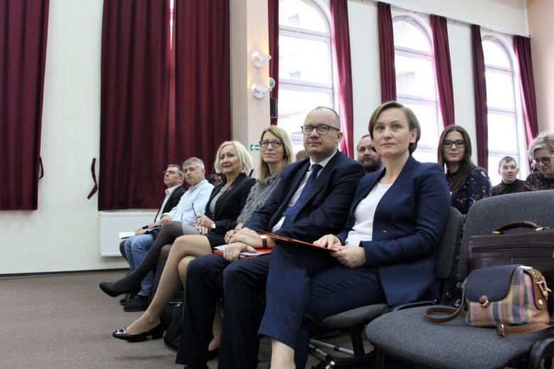Osoby siedzą na sali