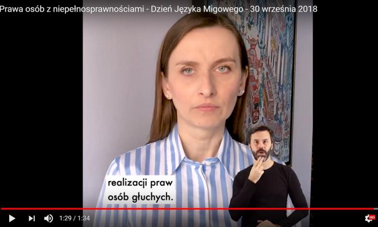 Screen z wystąpienia kobiety. na youtube. Na dole sylwetka tłumacza migowego