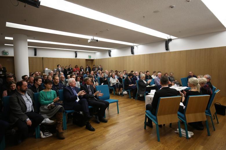Sala audytoryjna pełna ludzi, zielone krzesla