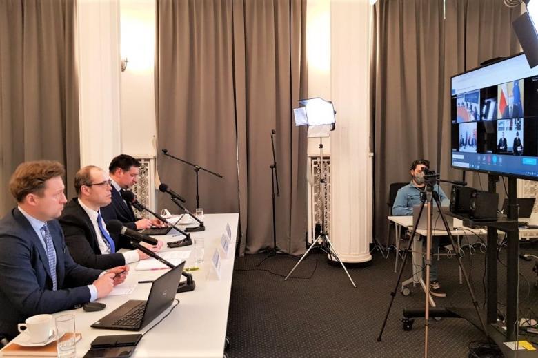 trzej mężczyźni biorą udział w telekonferencji