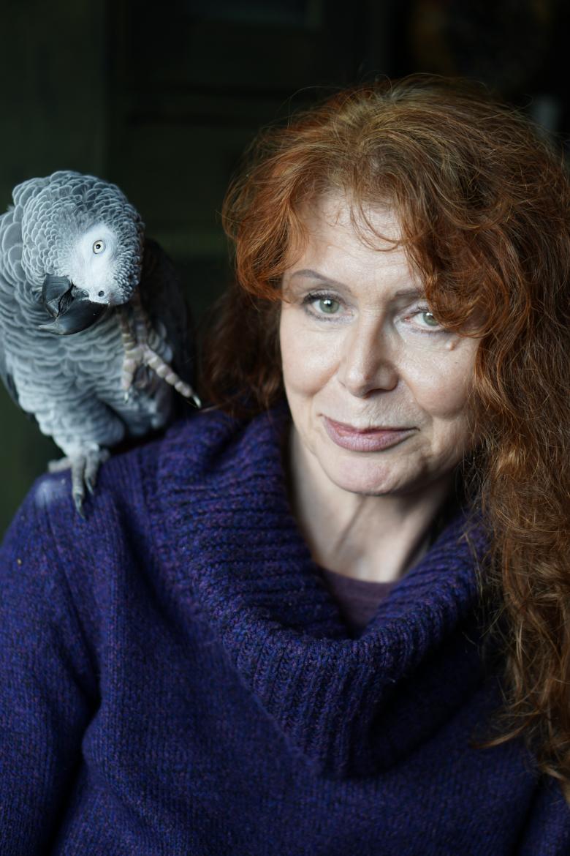 kobieta o rudych kręconych włosach z papugą na ramieniu