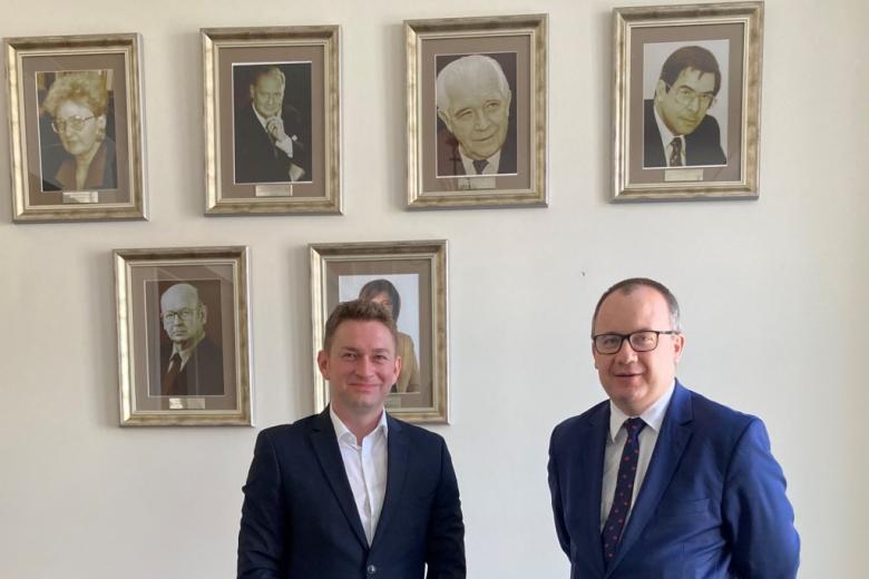 Dwaj męzczyźni na tle ściany z portretami rzeczników praw obywatelskich