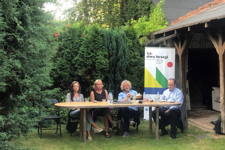 Cztery osoby siedzą za stołem w ogrodzie koło domu