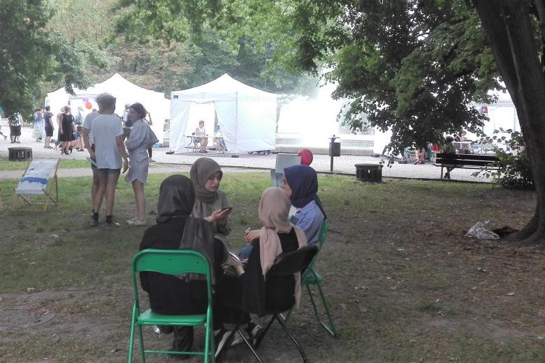 Osoby siedzą w parku