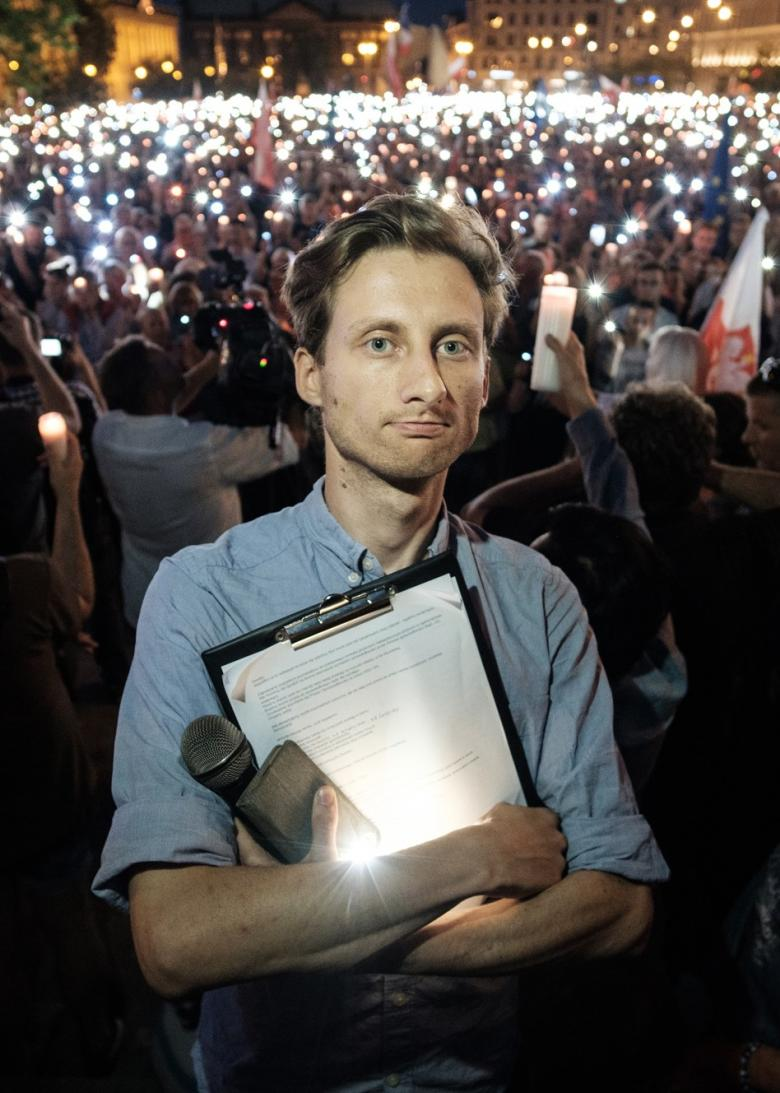 Mężczyzna z podkładką na dokumenty na tle zgromadzonych ludzi ze świecami