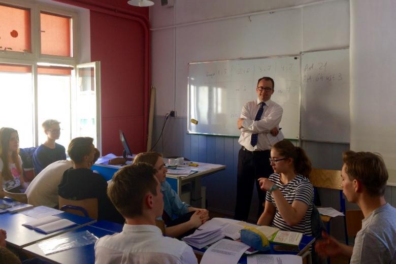 zdjęcie: mężczyzna w białej koszuli i krawacie stoi pomiędzy ławkami, przy których siedzą uczniowie
