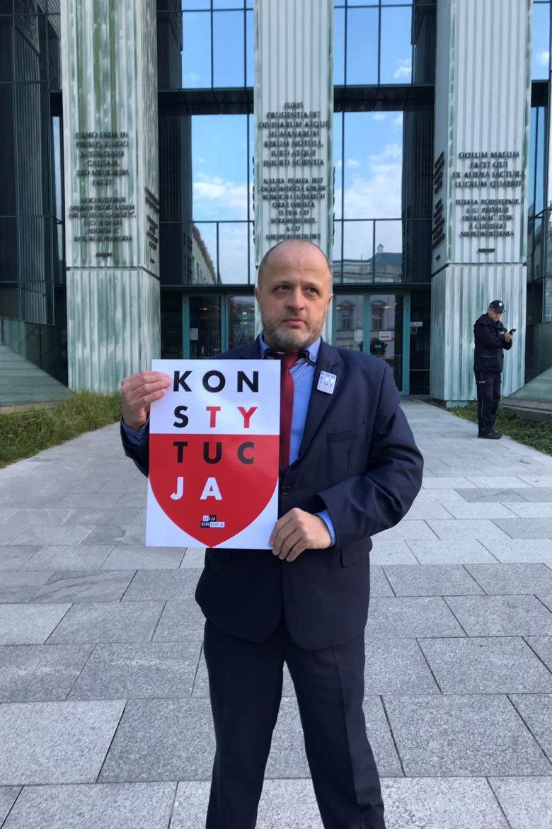 Mężczyzna z plakatem KonsTYtucJA na tle Sądu Najwyższego
