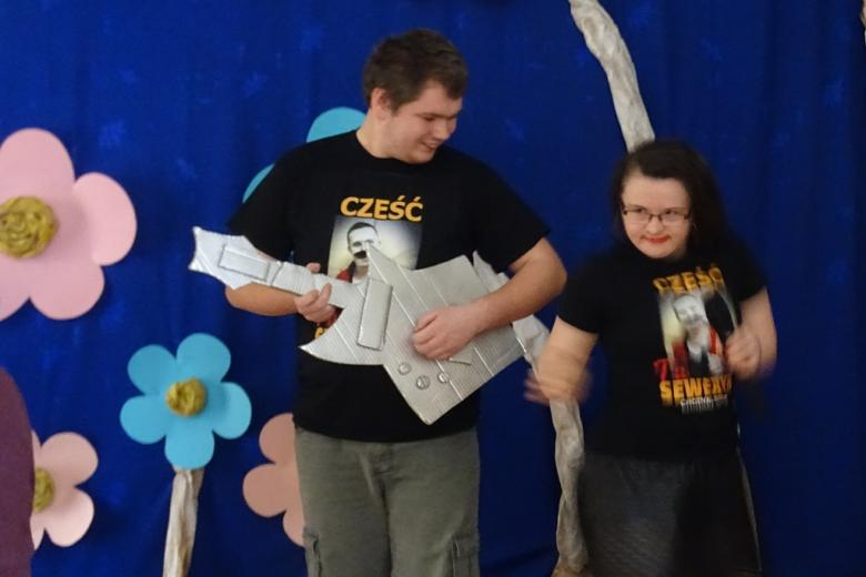 Chłopak z papierowa gitarą i dziewczyna z mikrofonem (oboje z niepełnosprawnością) uśmiechają się do siebie