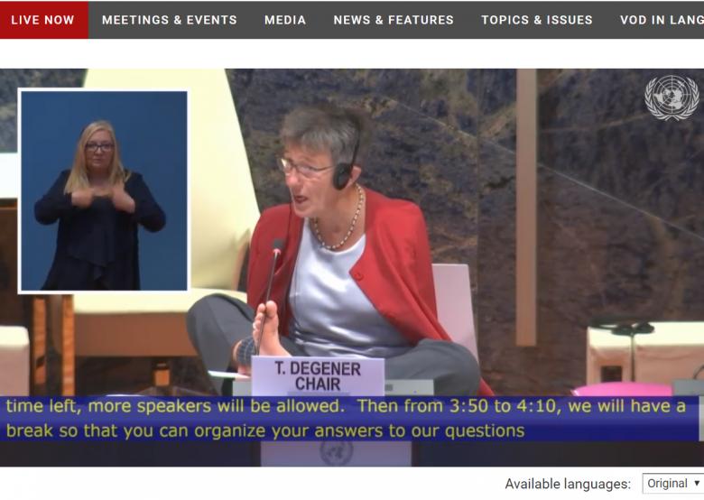 Scrren z transmisji. Przewodnicząca w czerwonym żakiecie, kobieta bez rąk, sprawnie przegląda dokumenty posiedzenia przy pomocy nóg