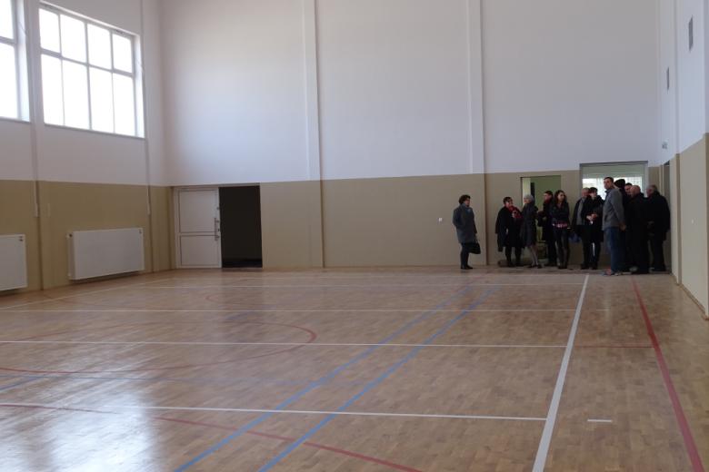Grupa ludzi w pustej hali sportowej