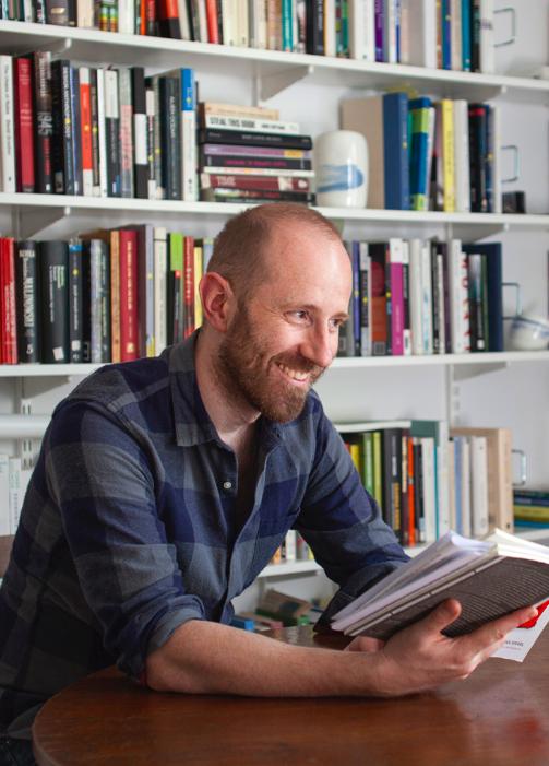 Mężczyzna z brodą na tle regału z książkami