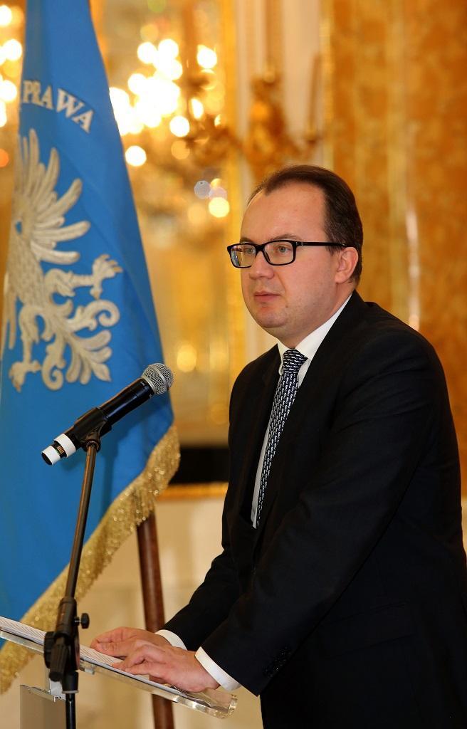 zdjęcie: mężczyzna w garniturze stoi przy mównicy