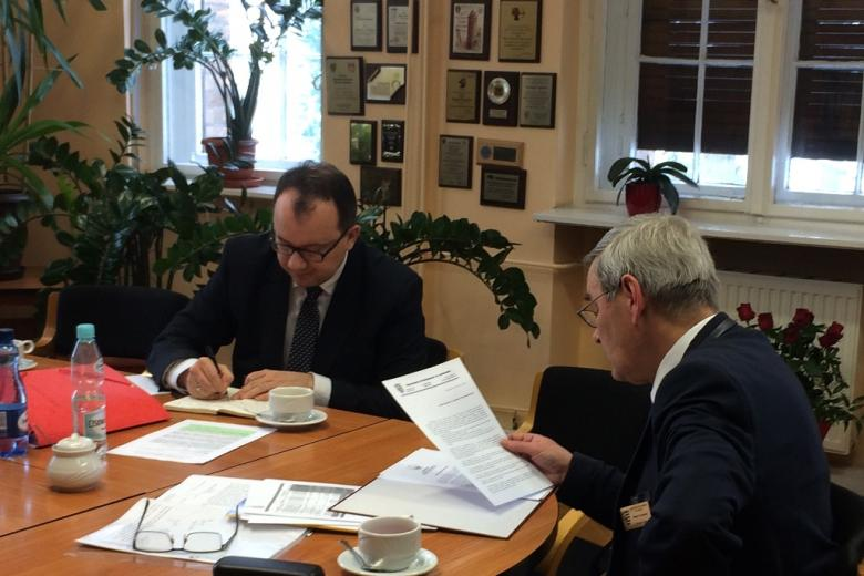 zdjęcie: dwóch mężczyzn siedzi przy stole i przegląda dokumenty