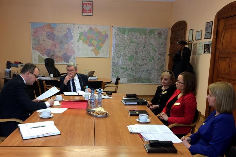 zdjęcie: przy owalnym brązowym stole siedzi dwóch mężczyzn i trzy kobiety