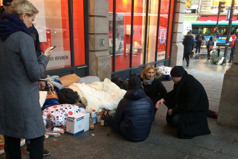 zdjęcie: przy koczowisku na ulicy kuca mężczyzna i kobieta, tyłem na ziemi siedzi mężczna w kurtce
