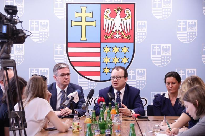 zdjęcie: dwaj mężczyźni i kobieta siedzą za stołem, na stole mikrofony