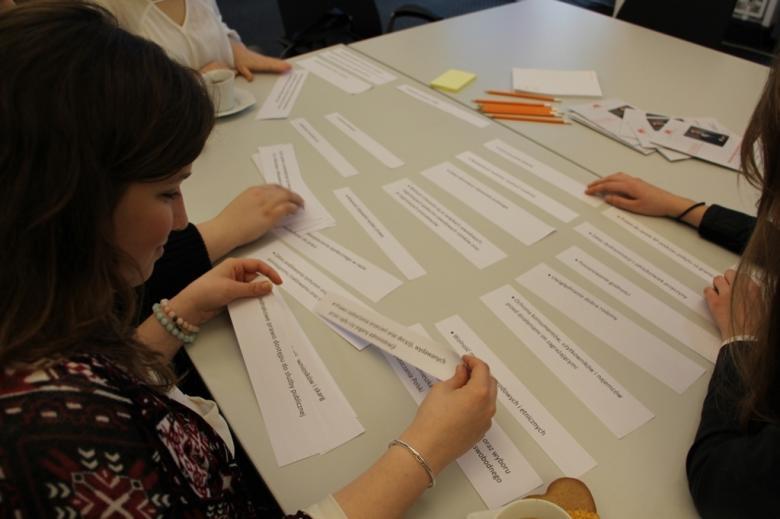 na zdjęciu uczestnicy warsztatów siedzą wokół stołu i przeglądają wycinki z zadaniami