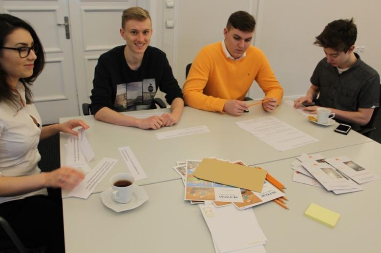 na zdjęciu uczestnicy warsztatów siedzący przy stole i rozwiązujący zadanie