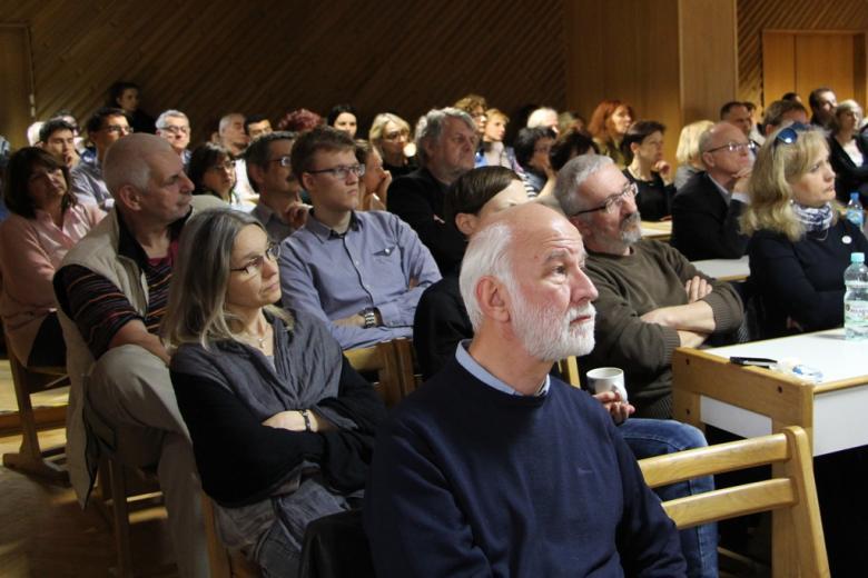 zdjęcie: ludzie w różnym wieku siedzą w rzędach i ze skupieniem słuchają wykładu