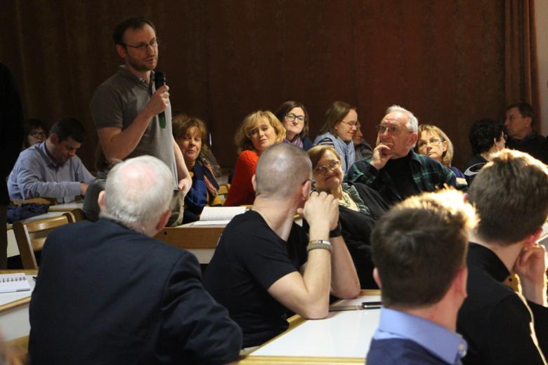 zdjęcie: mężczyzna stoi i przemawia do mikrofonu, inne osoby siedzą i są zwrócone w jego stronę