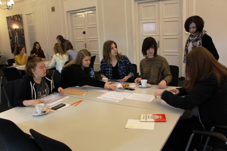 zdjęcie: pięć dziewczyn siedzi wokół kwadratowego stołu, na stole leży biało-czerwona książka z napisem Konstytucja Rzeczypospolitej Polskiej