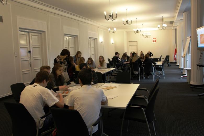 zdjęcie: duża sala,młodzież podzielona na kilkuosobowe grupy siedzi przy kilku kwadratowych stołach