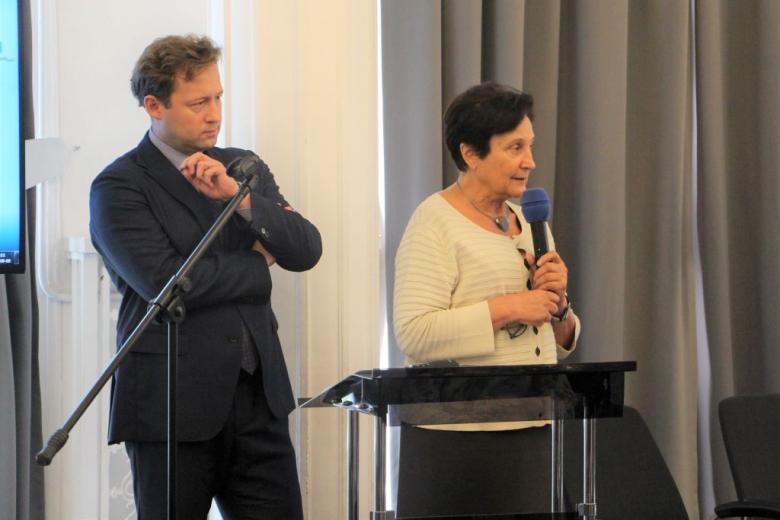 Na zdjęciu mężczyzna i kobieta stoją, kobieta mówi do mikrofonu