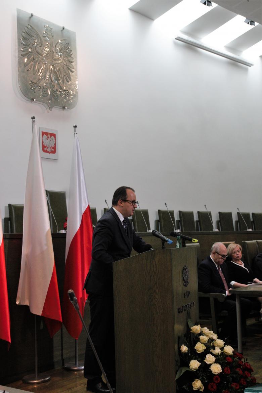 Mężczyzna stojący na mównicy podczas przemowy