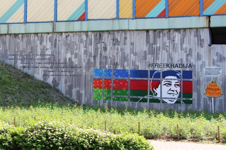 zdjęcie: na muralu widać białą twarz kobiety, jest namalowana na tle niebiesko, czerowno, zielonych pasów