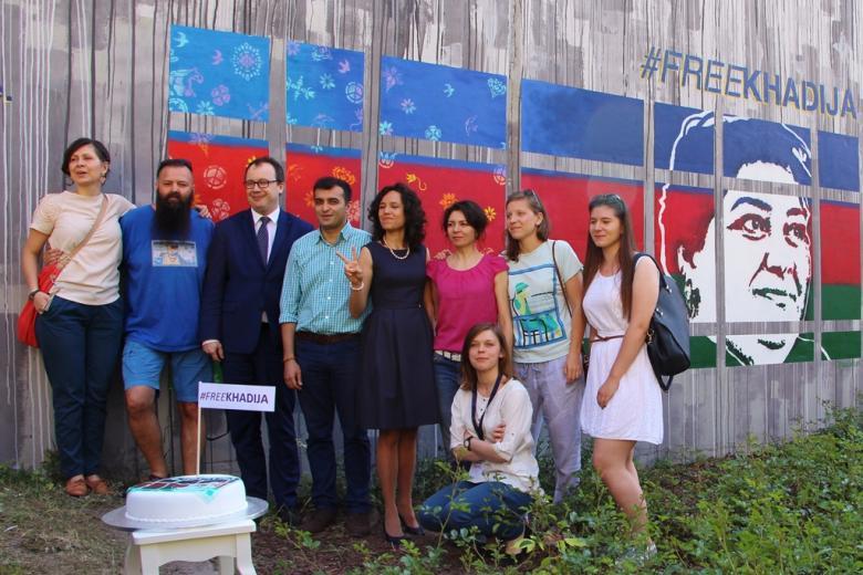 zdjęcie: grupa osób stoi na tle muralu, przed nimi na białym stoliczku stoi tort