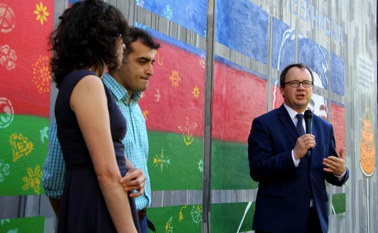 zdjęcie: na tle muralu w niebiesko-czerwono-zielonych barwach, stoją dwaj mężczyźni i jedna kobieta, mężczyna po prawej - w granatowym garniturze przemawia do mikrofonu