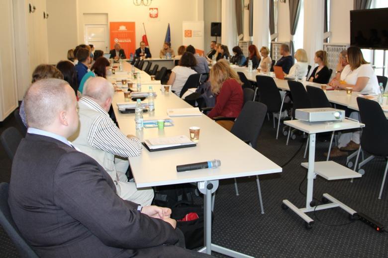 zdjęcie: duża grupa ludzi siedzi przy stołach ustawionych w kształcie podkowy