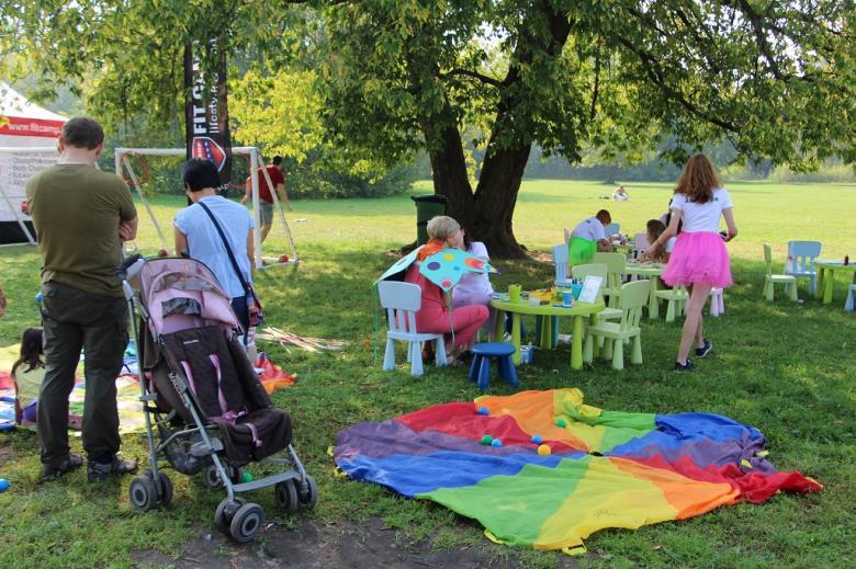 zdjęcie: na trawie lezy kolowory koc, w tle widać małe kolorowe krzestałka i stoliki przy których siedzą dzieci