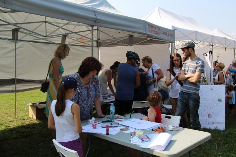zdjęcie:widać stolik przy którym siedzą dzieci, w tle białe namioty i dorośli