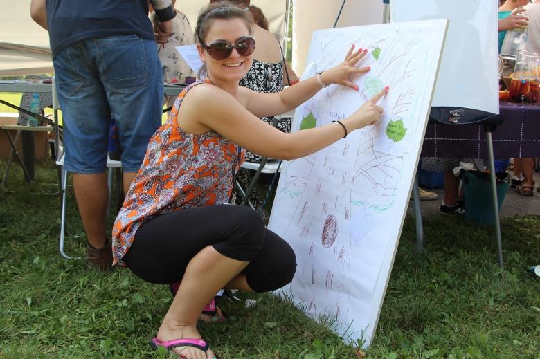 zdjęcie: uśmiechnięte kobieta kuca, by przykleić kartkę do stojącej na ziemi tablicy