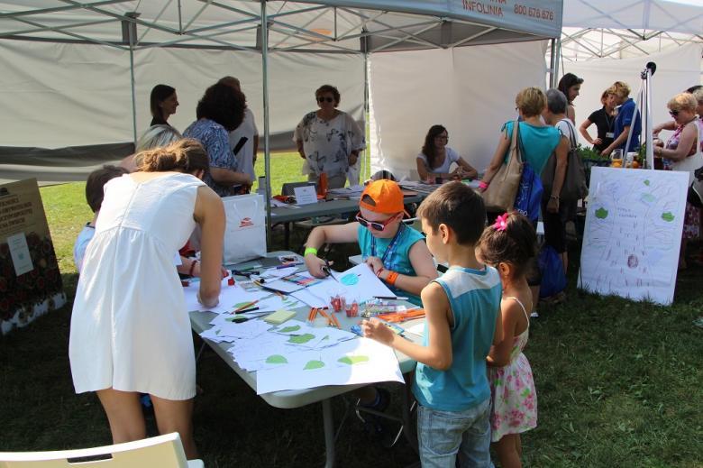 zdjęcie: kilkorodzieci koloruje liście i pisze o prawach człowieka, ich pracy przygladają się dorośli