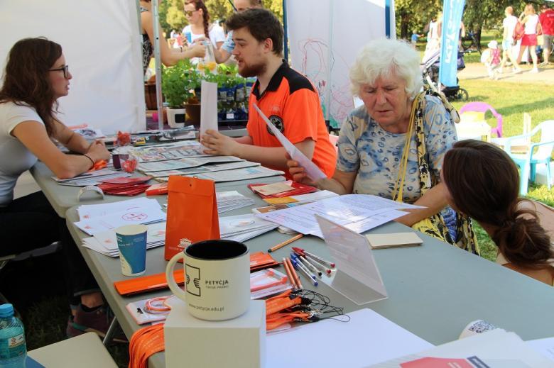 zdjęcie: ratownik w pomarańczowym stroju i starsza pani dyskutują przy stole z dwoma kobietami