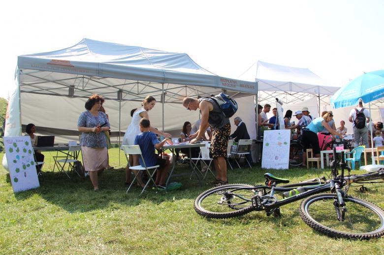 zdjęcie: na pierwszyym planie lezy rower, w tle widać ludzi stojących prz namiocie