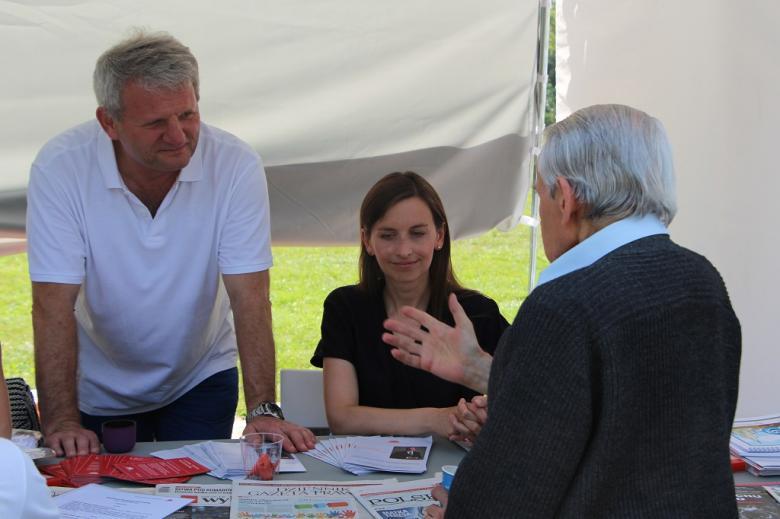 zdjęcie: starszy mężczyzna gestykuluje rozmawiając z kobietą i mężczyzną po drugiej stronie stołu