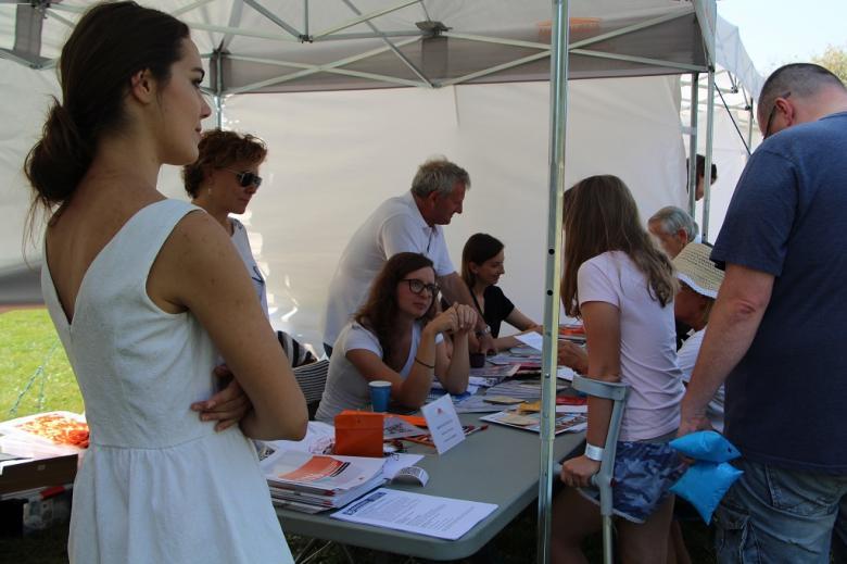 zdjęcie: kilka osób stoi przy stoliku i czyta ulotki