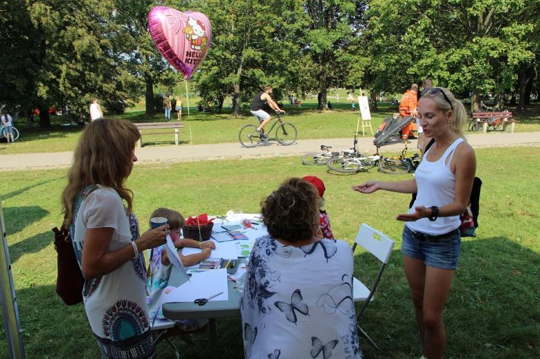 zdjęcie: dziwczynka z rożowym balonem rysuje przy stoliku, obok są też dorośli