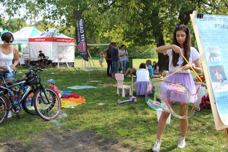 zdjęcie: nastolatka robi duże bańki mydlane, w tle widać bawiące się dzieci