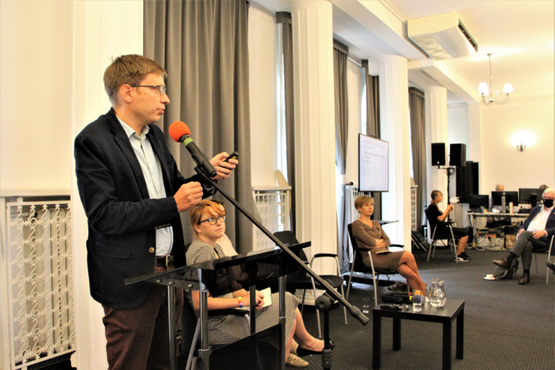Uczestnicy konferencji w maseczkach na twarzy słuchają panelisty