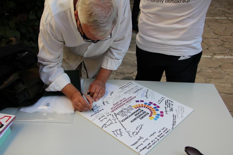 Mężczyzna w białej koszuli podpisuje plakat z podziękowaniami dla RPO