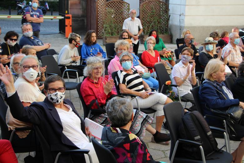 tłum ludzi w kolorowych maseczkach i ubraniach słucha czytanego listu